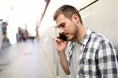 Side View Portrait Of A Sad Man Talking On Phone Alone In A Solitary Street poster