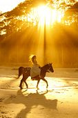 foto of bareback  - backlit woman in formal dress riding horse on beach - JPG
