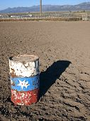stock photo of barrel racing  - An old painted barrel in a rural rodeo arena - JPG