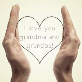 stock photo of grandpa  - someone holding a drawn heart in his hands and the sentence I love you grandma and grandpa written in it - JPG