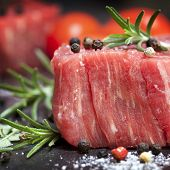 stock photo of peppercorns  - Raw beef steak with peppercorns and herbs - JPG