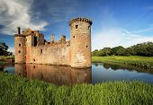 stock photo of castle  - Caerlaverock Castle reflecting on the moat that surrounds the castle - JPG