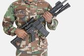 stock photo of m4  - Midsection of US Marine Corps soldier holding M4 assault rifle over gray background - JPG