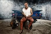picture of guitarists  - Guitarist at a garage next to the retro car in smoke - JPG