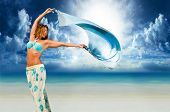 stock photo of windy  - Woman with sarong pareo on the beach - JPG