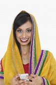 stock photo of dupatta  - Portrait of an attractive Indian female in traditional wear holding cell phone over white background - JPG