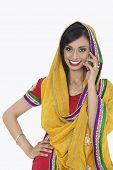 stock photo of dupatta  - Portrait of an Indian woman in traditional wear answering phone call over white background - JPG