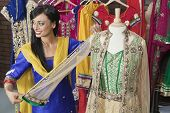 stock photo of dupatta  - Indian female dressmaker measuring traditional outfit at design studio - JPG