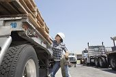 stock photo of logging truck  - Female industrial worker strapping down wooden planks on logging truck - JPG