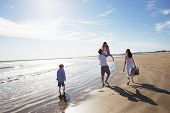 stock photo of barefoot  - Rear View Of Family Walking Along Beach With Picnic Basket - JPG