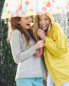 stock photo of 15 year old  - Two Teenage Girl Sheltering From Rain Beneath Umbrella - JPG