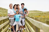 stock photo of old bridge  - Multi Generation Family Walking Along Wooden Bridge - JPG