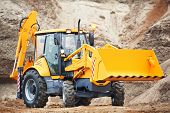 stock photo of risen  - Wheel excavator loader with risen bucket at eathmoving works in construction site or sandpit - JPG