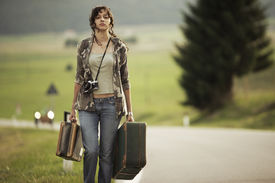 picture of runaway  - Young woman with suitcases runaway walks away road - JPG