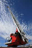 image of ladder truck  - Firefighter serving with the fire truck ladder extended.