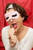 Attractive Woman In Sleeping Mask Imitates Singing Into A Microphone