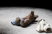 image of unclothed  - Stripped teddy lying on a concrete floor - JPG