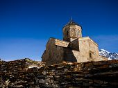stock photo of trinity  - The Gergeti Trinity Church under Kazbegi Mountain in north - JPG