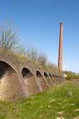 stock photo of dutch oven  - Ancient Dutch brick factory with brick kiln oven holes and chimney - JPG