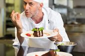 foto of pastry chef  - Closeup portrait of a smiling male pastry chef with dessert in the kitchen - JPG