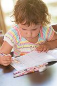 cute child girl studying, doing homework, at home or classroom