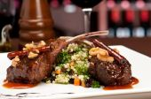 stock photo of lamb chops  - Close up of lamb chops with couscous and vegetables with a sauce of caramel pepper and spices in a restaurant setting - JPG