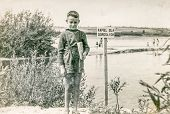 POLAND, CIRCA FORTIES - Vintage photo of little boy at lakeside. The sign says: Swimming only for ad