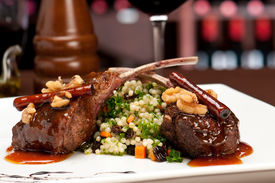 stock photo of gourmet food  - Close up of lamb chops with couscous and vegetables with a sauce of caramel pepper and spices in a restaurant setting - JPG