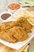 picture of southern fried chicken  - Fried Chicken & Chips - Chicken pieces on the bone coated in a spicy flour and deep fried served with fries, baked beans and gravy.