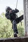 stock photo of anti-terrorism  - Spec ops soldier in face mask during rope exercises with weapons