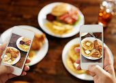 two friends taking photo of their food with smart phones poster