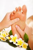 stock photo of reflexology  - Exotic foot massage and spa foot treatment - JPG