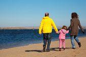 Постер, плакат: Семья из трех человек прогулки вдоль пляжа Вид со спины