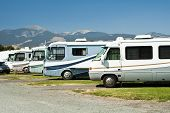 stock photo of motor coach  - recreational vehicles parked in a campground for a rally - JPG