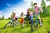 Постер, плакат: Happy kids in colorful bike helmets holding bikes