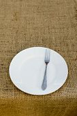 picture of collate  - Place setting with plate and fork against brown plate mat - JPG
