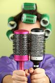stock photo of hair curlers  - Girl in hair curlers  holding hair combs on colorful background - JPG