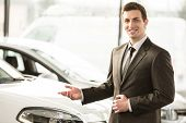 image of showrooms  - Young man consultant in showroom is standing near car - JPG