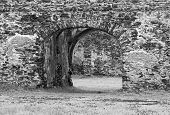 pic of monochromatic  - Monochromatic photo of of old ruins built with stone bricks with a gate with an arc in the center giving view across the ruins - JPG