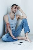 picture of heroin  - Depressed young man sitting on the floor with hand injured of the heroin injection - JPG