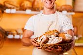 pic of apron  - Cropped image of young man in apron holding basket with baked goods and smiling while standing in bakery shop - JPG
