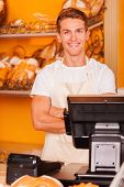 picture of cashiers  - Handsome young male cashier in apron keeping arms crossed and smiling while standing at the cash register in bakery shop