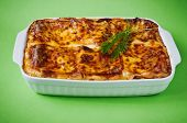 foto of lasagna  - freshly baked lasagna in a ceramic baking dish on a green background - JPG