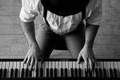 stock photo of compose  - Black and white top view image of man playing piano - JPG