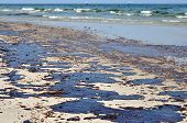 image of gulf mexico  - Oil spill on beach with oil skimmers in background - JPG