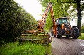 stock photo of grass-cutter  - mowing grass shoulder along road in public space  with big orange tractor mower  - JPG