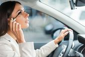 picture of side view  - Side view of young woman in formalwear doing make-up while driving a car ** Note: Soft Focus at 100%, best at smaller sizes - JPG