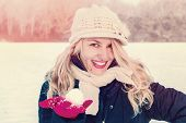 stock photo of cold-weather  - winter happy woman in snow holding snow ball on hand for snowballing outside on sunny cold winter vintage day - JPG