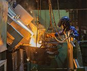 pic of furnace  - operator recieve molten metal from melting furnace - JPG