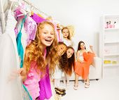 stock photo of stand up  - Happy cute girls in the shop choosing clothes while standing among hangers with colorful bright dresses and children clothes  - JPG